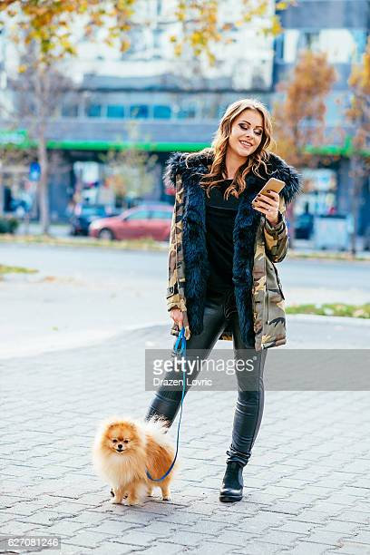 attractive woman walking the dog in city - pomeranian stock photos and pictures