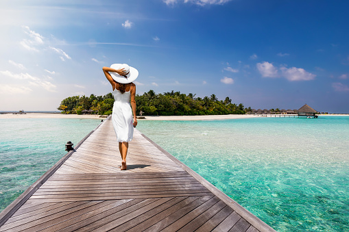 Attractive woman walks over a wooden jetty towards a tropical island 922825466