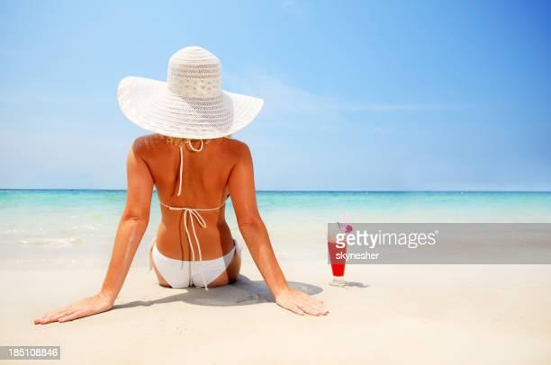 Atractiva mujer usando un sombrero en la playa frente a cielo.
