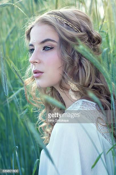 Attractive woman with blonde curly hair and blue eyes in nature