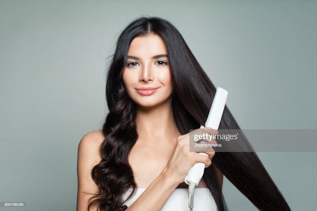 Attraktive Frau mit lockigem Haar und lange glatte Haare mit Haarglätter. Haarproblem und Haircare-Konzept : Stock-Foto