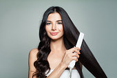 Attractive Woman with Curly Hair and Long Straight Hair Using Hair Straightener. Hair Problem and Haircare Concept