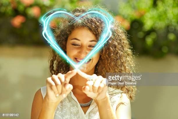 attractive woman with curly hair in a sleeveless top drawing a glowing heart in the air outside on a sunny day
