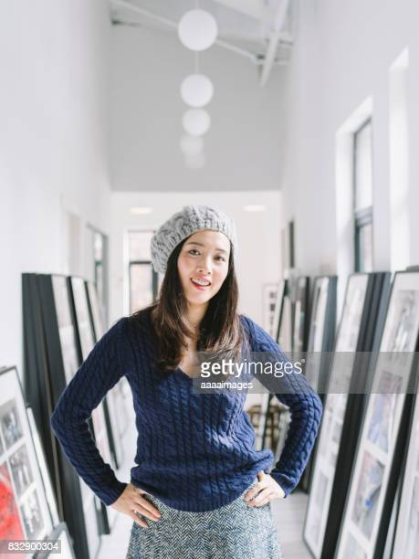 attractive woman with knit hat standing at gallery corridor