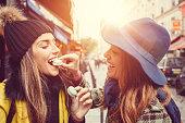 Attractive women eating parisian macaroons