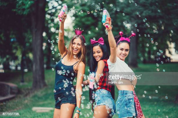 Attractive women making soap bubbles in the park