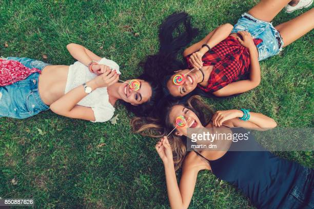 attractive women with lollipops in the park - lollipop stock pictures, royalty-free photos & images