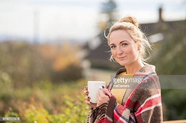 Attractive young adult female sipping coffee outside wearing blanket