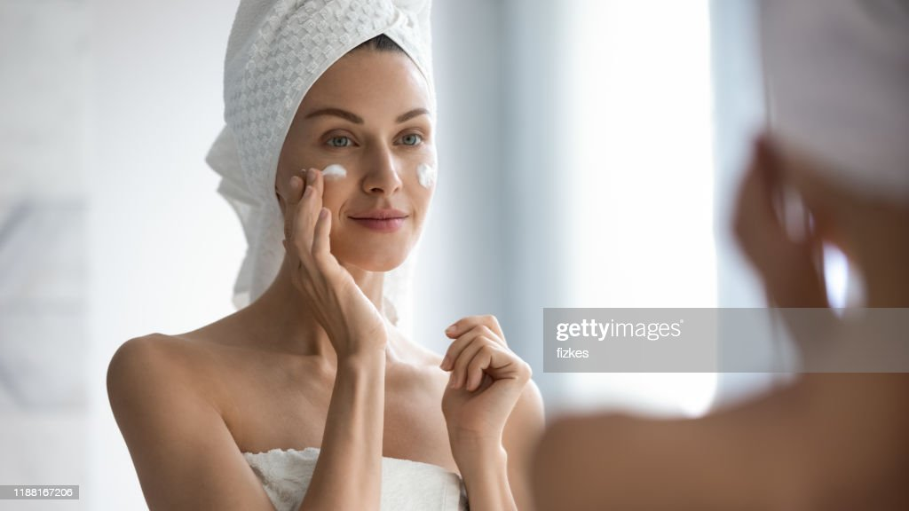 Attractive young adult woman applying facial cream looking in mirror : Stock Photo