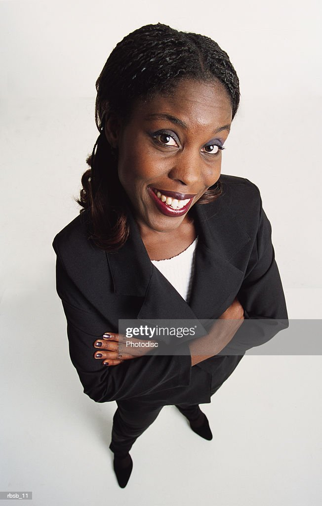 attractive young african american woman long dark hair dark suit stands looks to camera arms crossed : Foto de stock