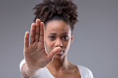 Attractive young African woman giving halt gesture
