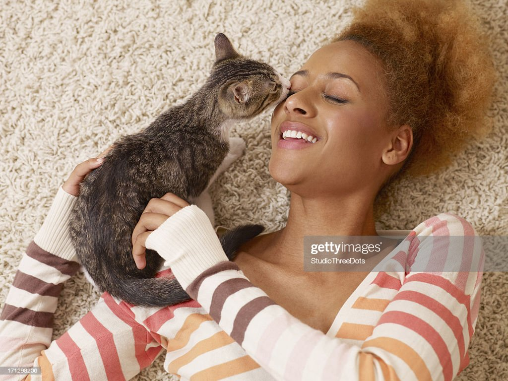 attractive young african woman laying on carpet with cat : Stock Photo