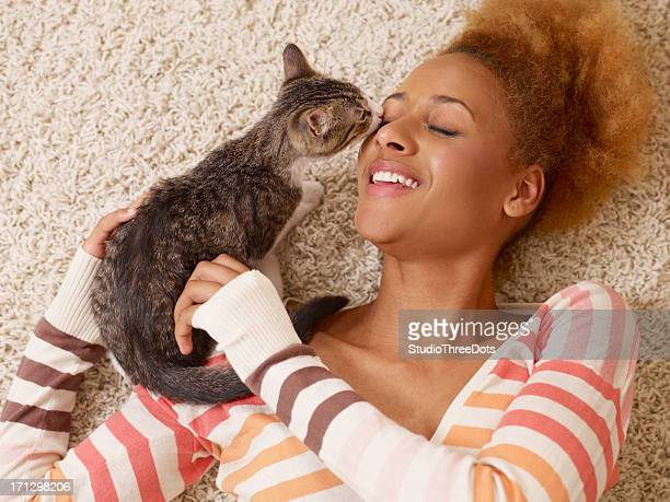 attractive young african woman laying on carpet with cat