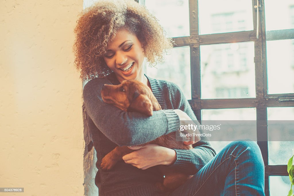 attractive young african woman playing with puppy : Stock Photo