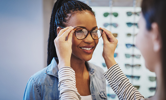 Attractive young African woman selecting glasses 520008622