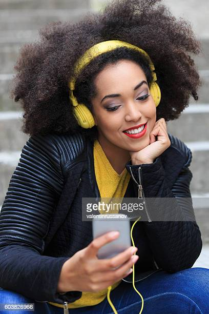 Attractive young african woman with yellow head phones