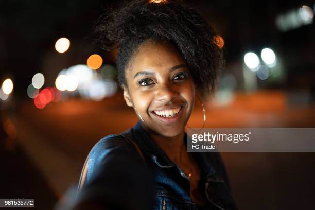 Attractive young afro woman holding hand of her boyfriend and walking in the city at night
