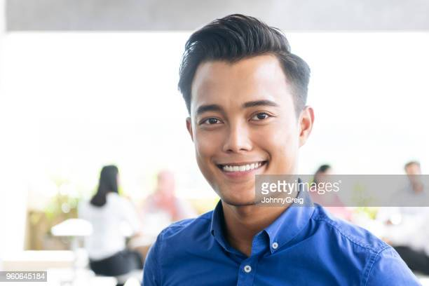 Attractive young Asian businessman smiling