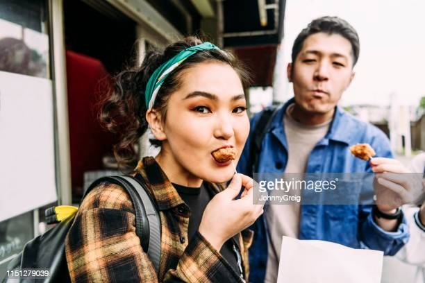 attractive young asian woman eating street food and looking at camera - tasting stock pictures, royalty-free photos & images