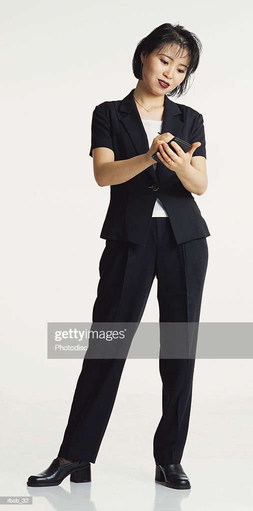 attractive young asian woman short hair in dark business suit stands faces camera using palm pilot : Foto de stock