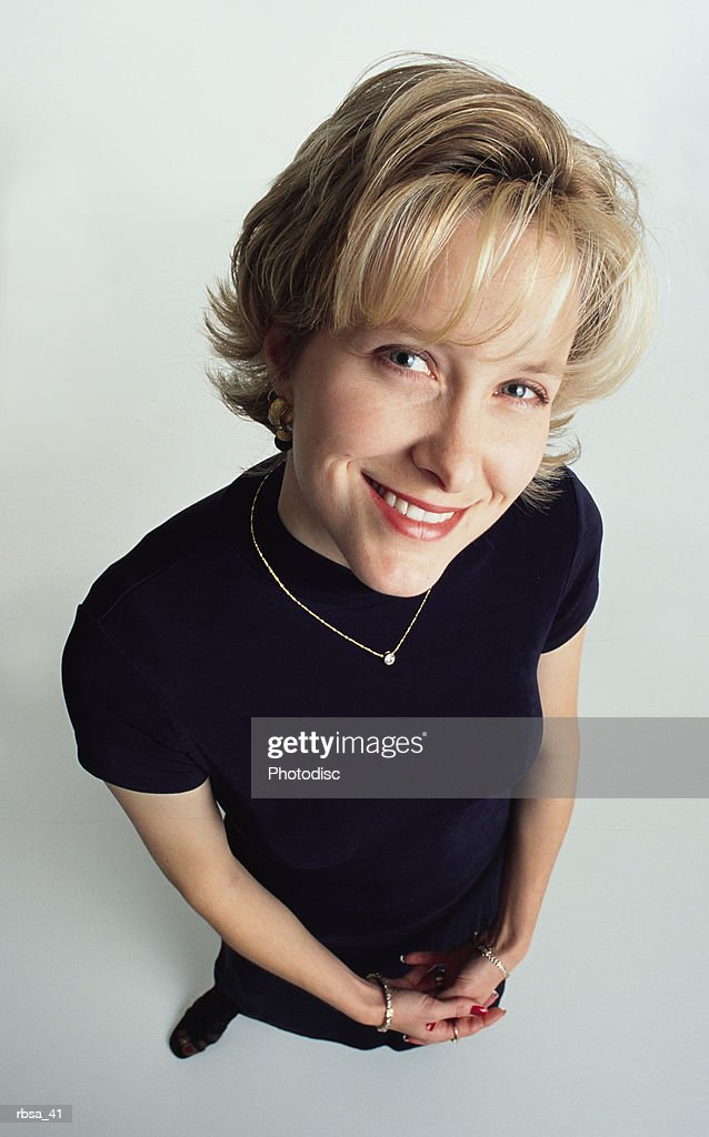 attractive young blonde caucasian adult female with short hair wearing a dark dress and diamond necklace stands looking up at the camera with a pretty smile : Foto de stock