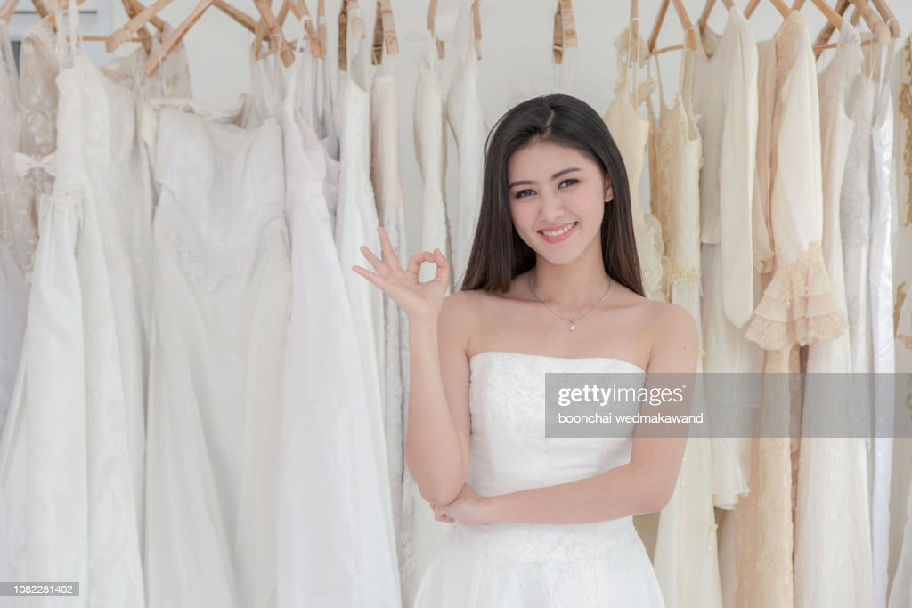 Attractive young bride is smiling while choosing wedding dress in modern wedding salon : Stock Photo