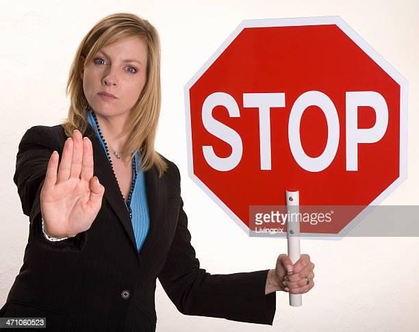 Séduisante jeune femme d'affaires détient un panneau «Stop»