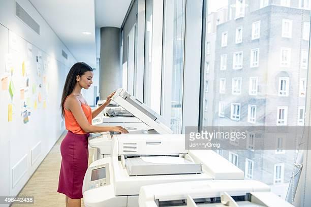 Séduisante jeune femme d'affaires avec une imprimante de bureau moderne