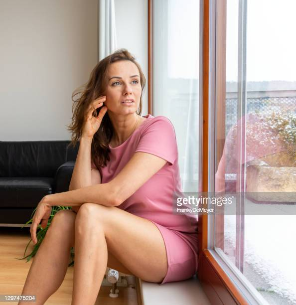 attractive young caucasian woman alone in home apartment, staring out of the large bright window of her apartment - mini dress stock pictures, royalty-free photos & images