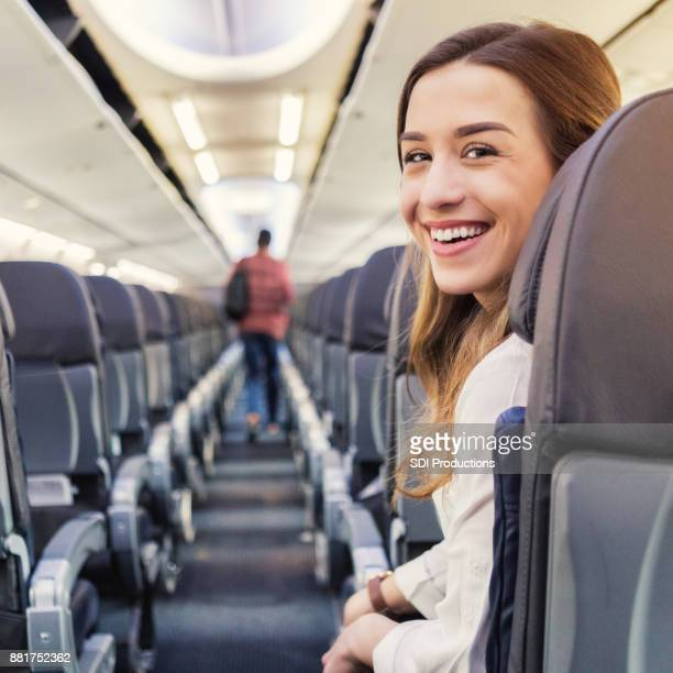 Attractive young Caucasian woman waits to disembark plane
