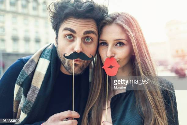 attractive young couple holding enormous red lips and black mustaches - comedian stock pictures, royalty-free photos & images