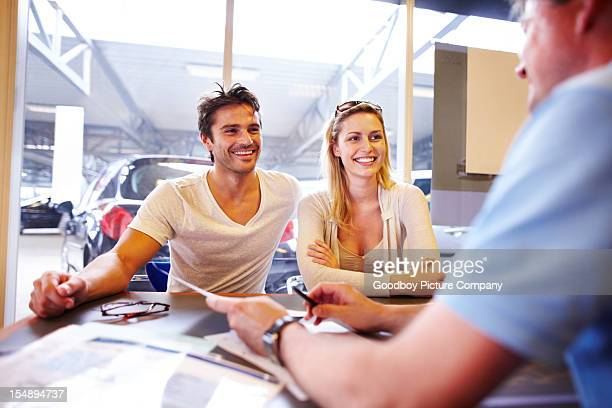 Attractive young couple in automobile showroom buying a new car