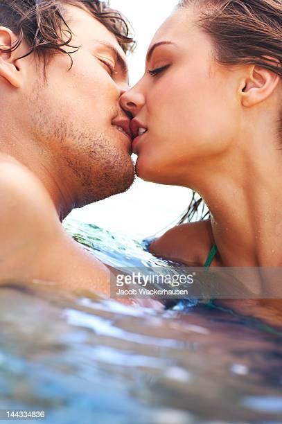 Séduisante jeune couple embrasser dans la mer