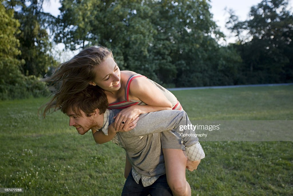 Attractive Young Couple playing Around in Park at Sunset : Stock Photo
