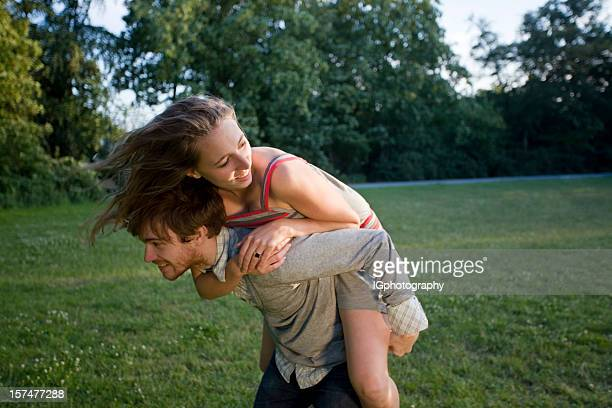 Attractive Young Couple playing Around in Park at Sunset