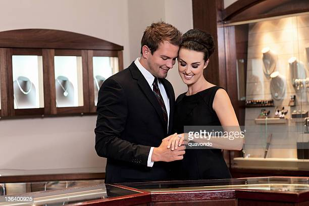 attractive young couple shopping for diamond wedding ring - jewelry store stock pictures, royalty-free photos & images