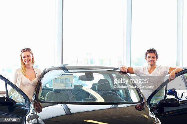 Attractive, young couple with their new car at showroom