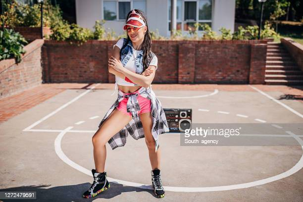 attractive young female dancer posing on the basketball court outdoors - hip hop music stock pictures, royalty-free photos & images