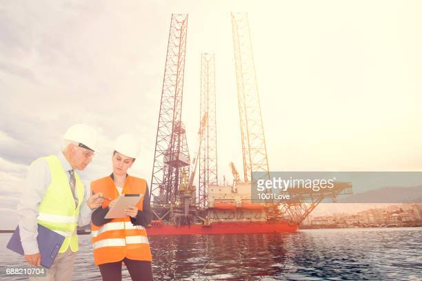 Attractive young female engineer and her boss, Offshore construction platform