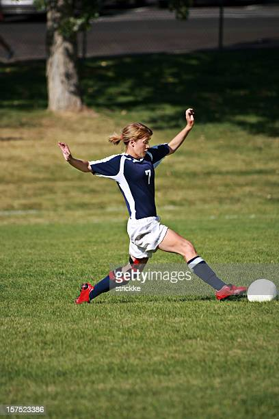 Attractive Young Female Soccer Player Stretches to Touch Ball