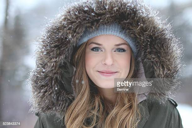 Attractive Young Female with Fur Hooded Jacket in Snowfall