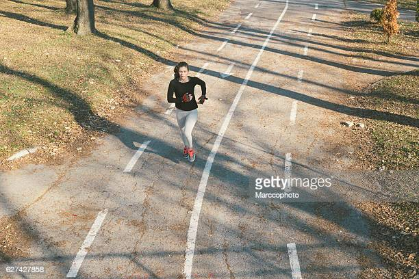 Attractive young girl exercising, jogging, early in the morning