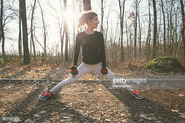 attractive young girl exercising outdoors, stretching legs on the ground - frau gespreizte beine stock-fotos und bilder