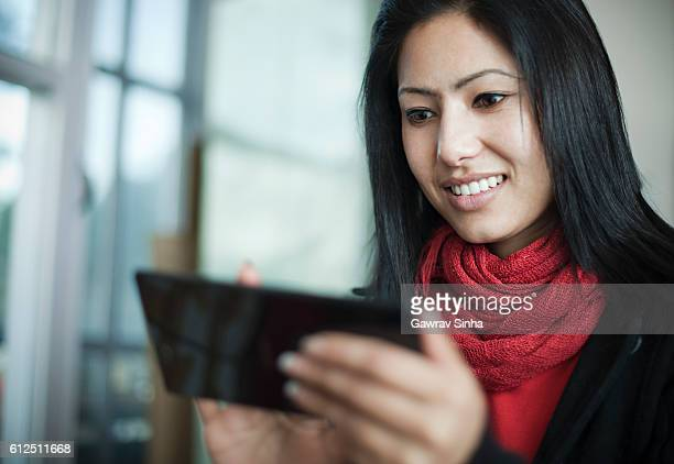 Attractive, young, happy Asian woman using smart phone or phablet.