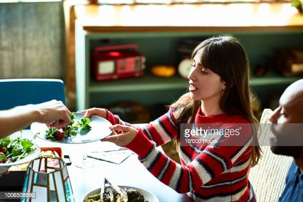 attractive young hispanic woman being served salad at dinner party - vegan food stock photos and pictures