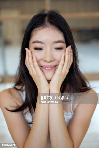 Attractive young Japanese woman holds her face in hands and smiling