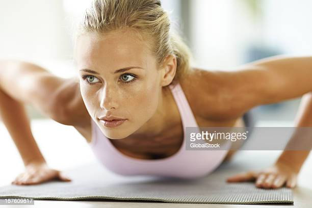 Attractive young lady doing push ups on exercise mat