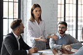 Attractive young mentor businesswoman conducts coaching in boardroom.