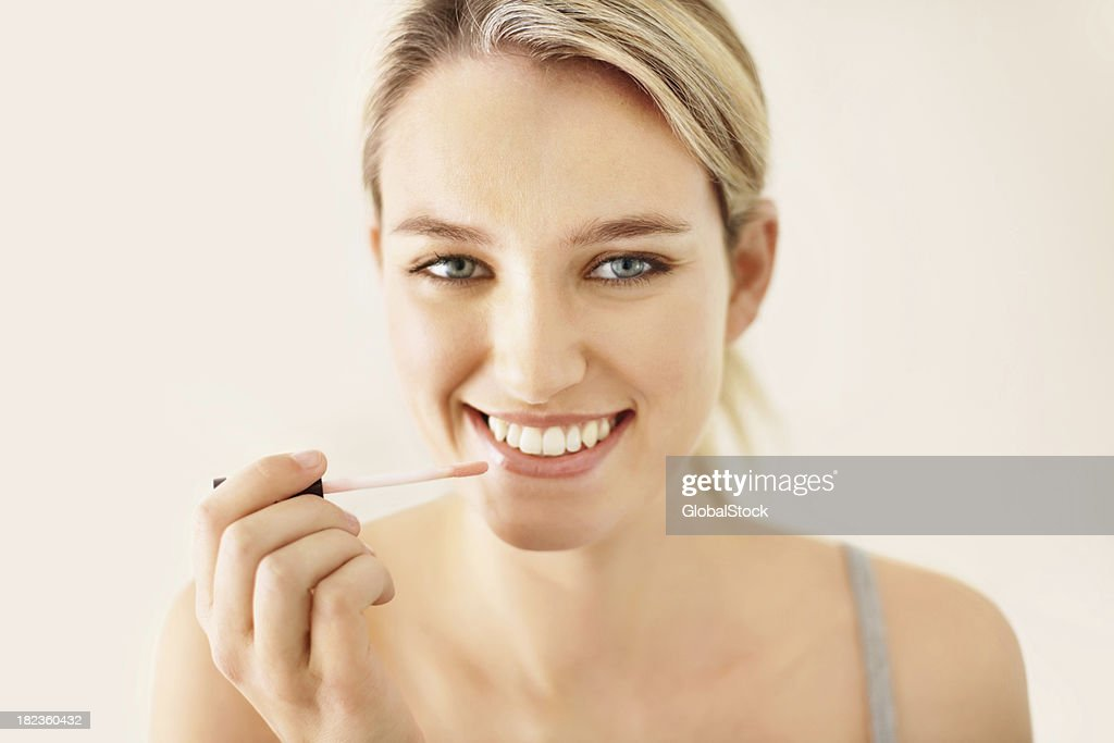 Attractive young woman applying lip gloss : Stock Photo