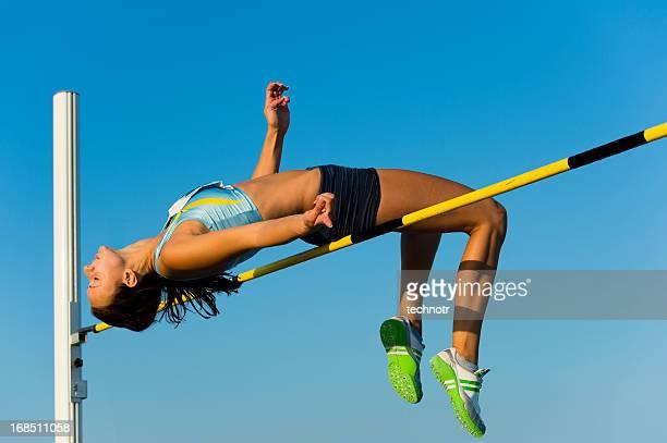 Belle jeune femme au saut en hauteur